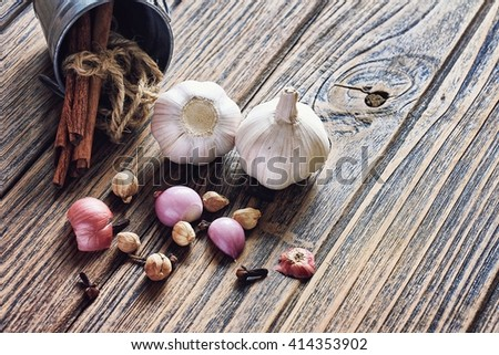 Variety of herb and spices on wooden background. Shallot, Cardamom, Cinnamon sticks, Fresh garlic. Healthy ingredients, Cuisine ingredients. (Color Process) - stock photo