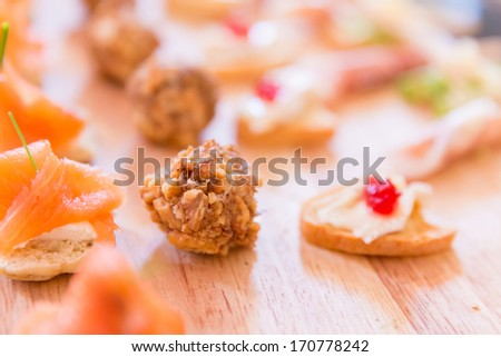 Variety of Hors D'oeuvres on a wooden platter - stock photo