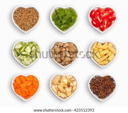 variety of ingredients in a heart shaped bowl, isolated on white coriander seeds, mint leaves, olive tomato, cucumber, mushroom, baby corn, sliced carrot, fresh ginger, star anise