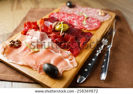 Variety of meats, sausages, salami, ham, olives, laid out on a wooden board close-up, horizontal, are next to a knife and fork - stock photo