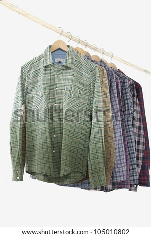 Variety of Men's different sleeved plaid cotton on a wooden hanger - stock photo