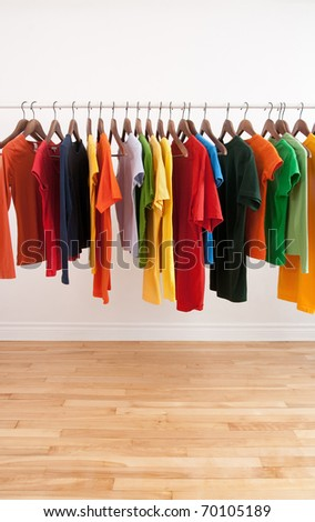 Variety of multicolored casual clothes on a rod, in a bright room.
