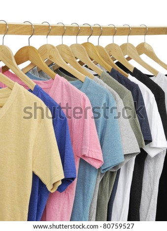 Variety of multicolored casual shirts on wooden hangers, - stock photo
