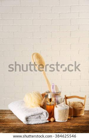 Variety of natural bath tools on wooden table, on bricks wall background