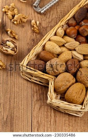 Variety of nuts with nut cracker, selective focus - stock photo