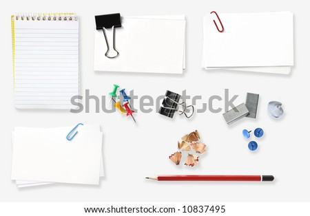 Variety of office stationery, isolated on white.  Includes spiral notebook, blank labels, bulldog clip, push pins, staples, pencil and pencil shavings, paperclip, blue tacky gum. - stock photo