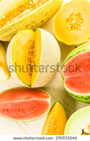 Variety of organic melons sliced on wood table.