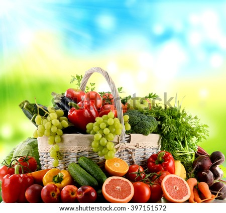 Variety of organic vegetables and fruits in wicker basket - stock photo