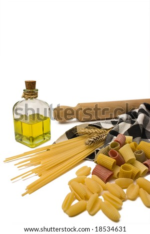 Variety of pasta with a rolling pin and olive oil. - stock photo