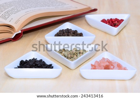 Variety of peppercorns and salt with open cook book in background