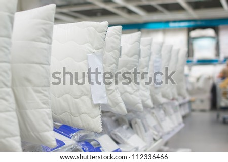 Variety of pillows on stands and shelves in mall