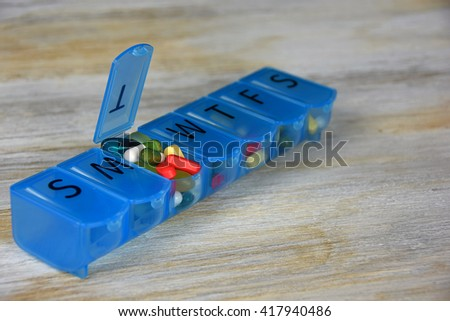 variety of pills in blue plastic pill organizer on weathered wood