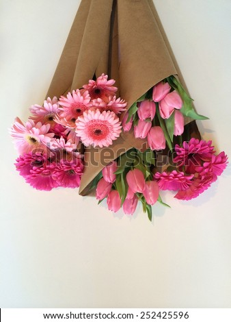 Variety of pink flowers wrapped in brown paper - stock photo