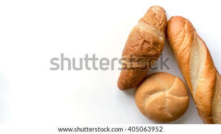 Variety of popular bread for breakfast on white background with shadows. Fresh french baguette, croissant and the bun. Top view - stock photo