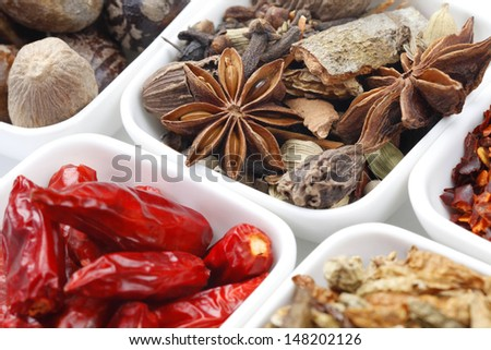 Variety of raw Authentic Indian Spices on square bowl on white background.  - stock photo