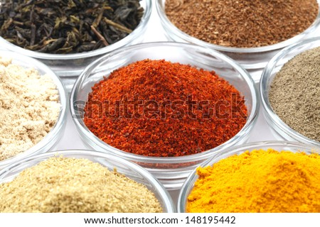 Variety of raw Authentic Indian Spices Powder on glass bowl isolated on white background in full-frame. Focus on chilli powder. - stock photo