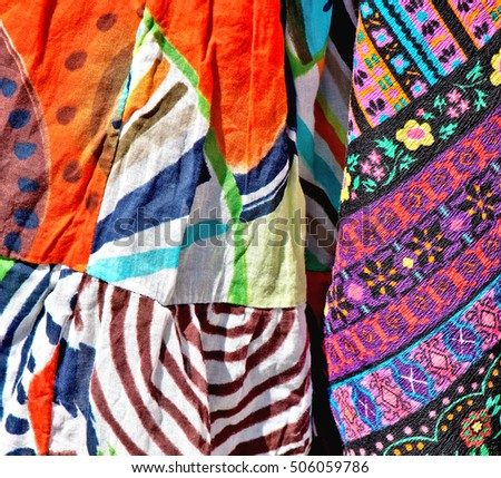 Variety of samples of bright, colorful silk fabric in oriental style for a decoration, needlework and  clothes purposes. A street bazaar at a flea market in Tel Aviv. Israel