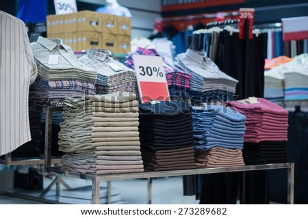 Variety of shirts on hangers and jeans on tables in clothes store - stock photo
