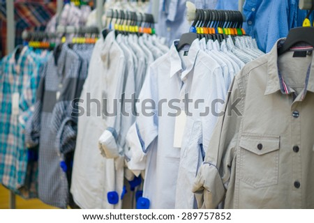 Variety of shirts on hangers in supermarket - stock photo