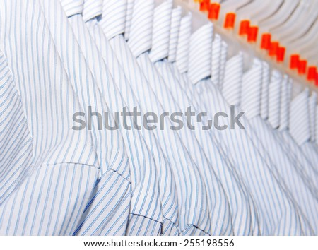 Variety of shirts on stands in mall - stock photo