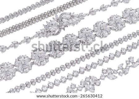 Variety of silver jewellery items on white background - stock photo