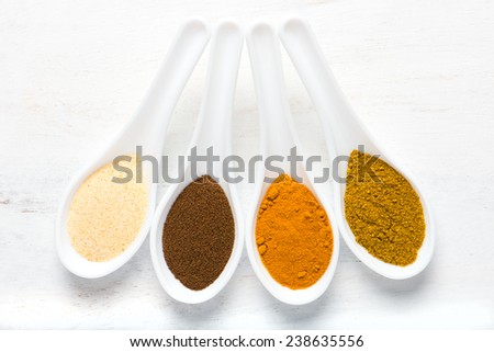 variety of spices (allspice, turmeric, garlic powder, curry) in white spoons, overhead view. - stock photo