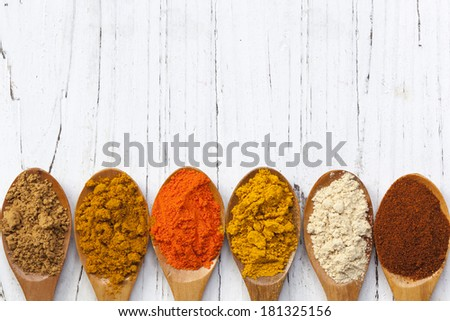 Variety of spices on wooden spoons, over distressed white timber.  Overhead view. - stock photo