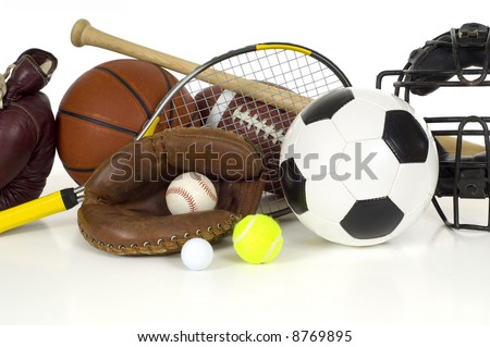 Variety of sports equipment on white background with copy space, items inlcude boxing gloves, a basketball, a soccer ball, a football, a baseball bat, a catcher's mitt or glove - stock photo