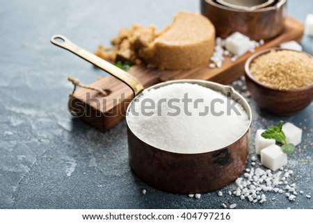Variety of sugar on the table with white, dark brown, cubed and pearl - stock photo