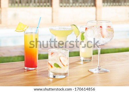 Variety of summer cocktails by the poolside - stock photo