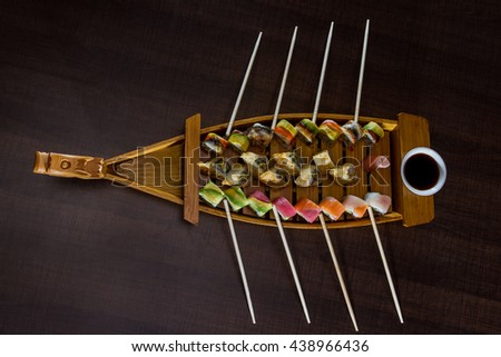 variety of sushi rolls served on a wooden boat - stock photo