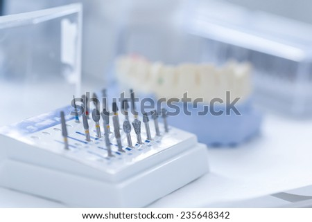 Variety of tools: ceramic preparation kit with dental mold in the background - stock photo