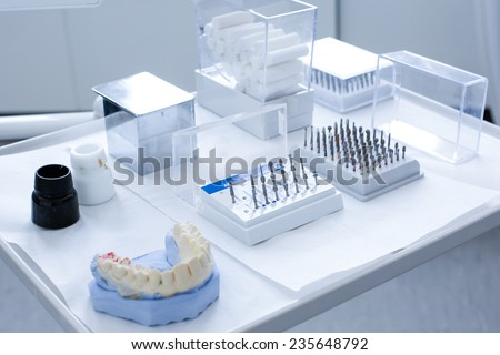 Variety of tools in dentist's office: ceramic preparation kit and various dental burs with dental mold on a tray - stock photo