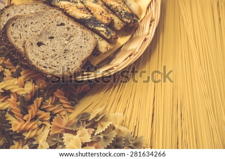 Variety of types and shapes of Italian pasta. Dry pasta background with slice of bread and salty sticks  - stock photo