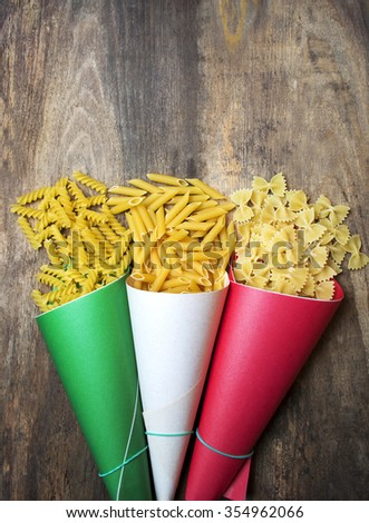 Variety of types and shapes of Italian pasta in paper envelopes Italy flag color . soft image, room for text. toned image - stock photo