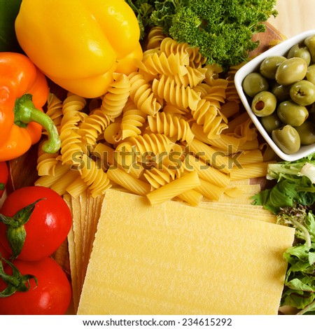 Variety of uncooced italian pasta on wodden table on brown wooden board
