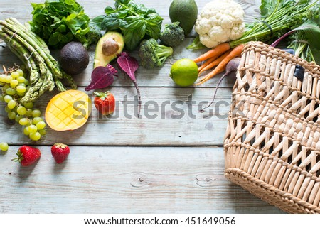 Variety of vegetables and fruits on rustic background, top view, horizontal border. Vegan food or diet eating concept. - stock photo
