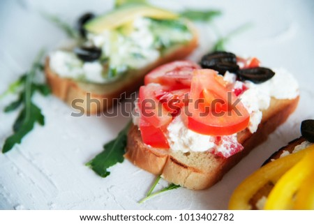 Variety of vegetarian bruschetta with fresh vegetables: toast, tomatoes, pepper, avocado, greens. The concept of healthy eating, vegetarianism.