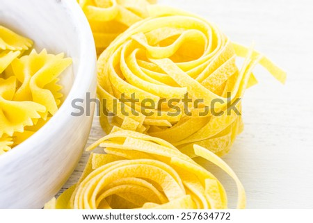 Variety of yellow dry pasta in small round bowls.