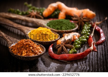 Variety spices in the spoons on wooden background - stock photo