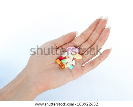 variety tablets on female hand retouched and isolated on smooth shadow background  - stock photo