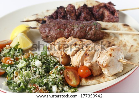 Various barbecued kebabs - kofta, chicken tawook and sumac chicken - with tabouleh and pitta bread; an Arab or Lebanese-style feast. - stock photo