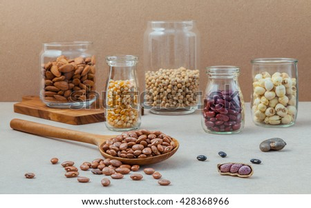 Various beans and nuts in the glass on brown background. mung bean, groundnut, red kidney bean , lotus seed ,almond,millet and brown pinto beans . - stock photo