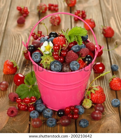 Various berries in a bucket on a brown background - stock photo