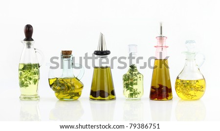 Various bottles of olive oil with herbs inside - stock photo
