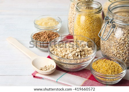 various cereals in glass jars and wooden spoon with glass bowls on a napkin on a white wooden table
