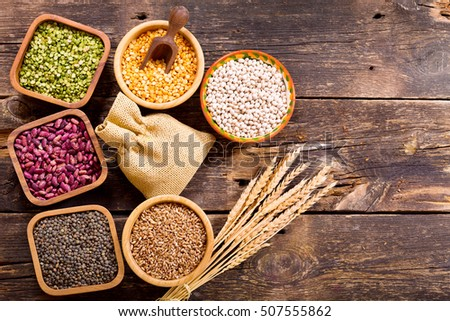 various cereals, seeds, beans and grains on wooden table, top view