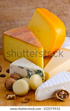various cheese types on a wooden plate