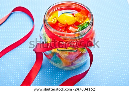 various child candies in a glass bowl with red ribbon over blue background with copy space - stock photo