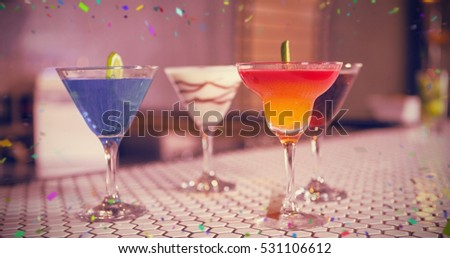 Various cocktails drinks on bar counter against flying colours